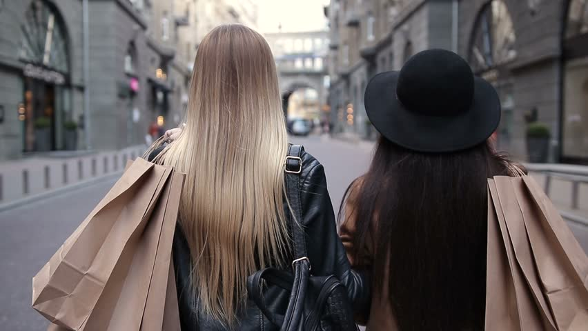 Back view of two walking women with shopping bags