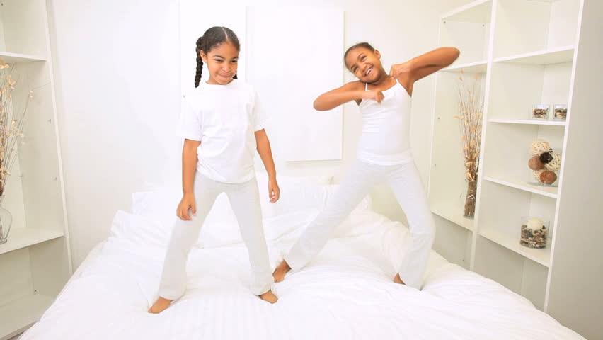 Young african american children bedroom dancing bed   HD stock video clip. African American Sisters Play Dancing Bed Home Bedroom Stock