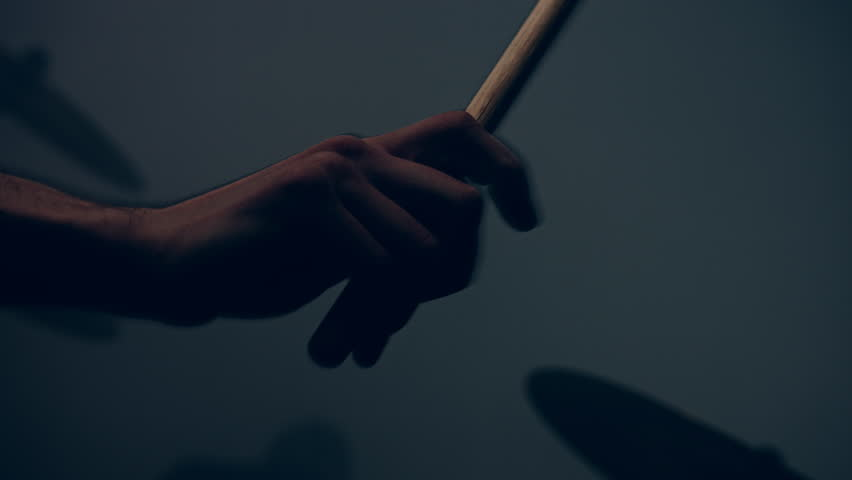 Drummer plays drums kit. Drummer hand silhouette with drumstick. Close up of drummer hand playing drum plate on rock concert. Rock band performing on stage. Close up of drum plate