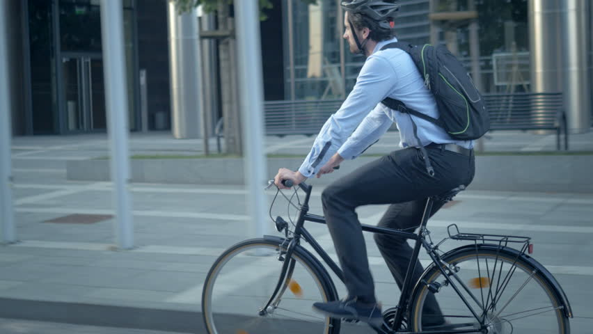Confident male worker in shirt with a backpack commuting to a job. Smart handsome cyclist traveling by sustainable transport and living a healthy lifestyle.