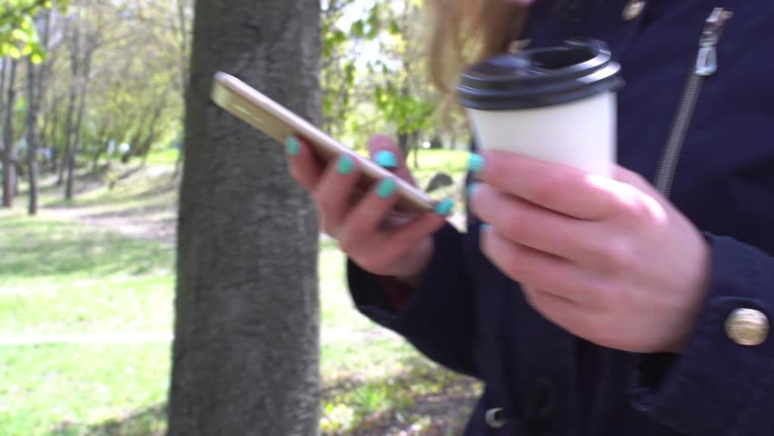 Talking on the phone, A girl is walking in the morning in a park with a smartphone and coffee steady camera shot    Shutterstock HD Video #26232932