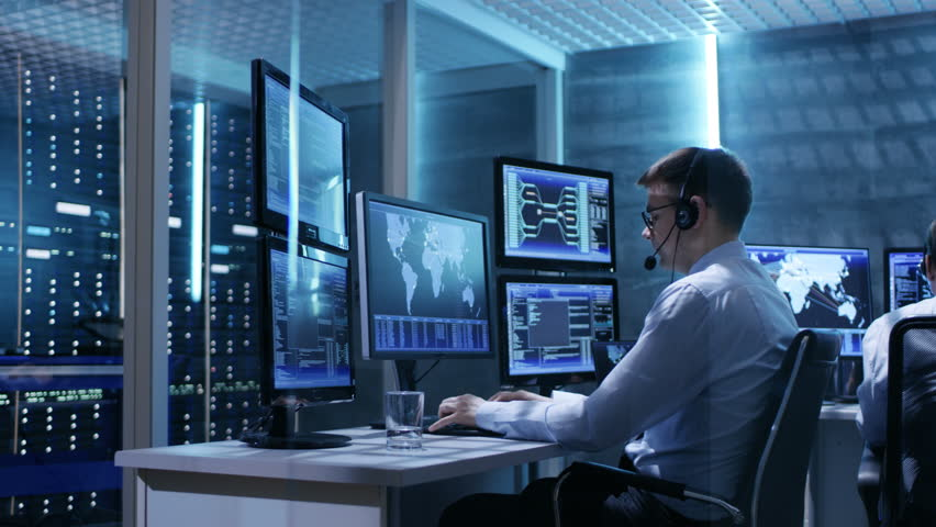 Panorama Shot of System Control Room with Three Technical Controllers Working at Their Workstations With Multiple Displays. Shot on RED EPIC-W 8K Helium Cinema Camera.   Shutterstock HD Video #26262950