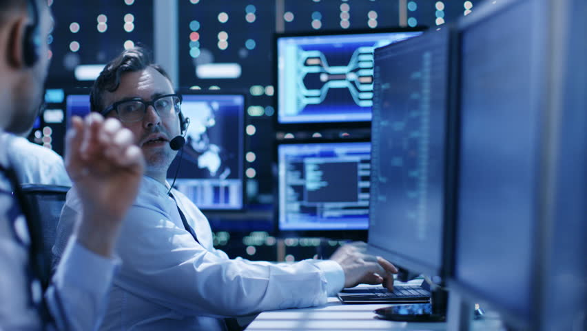 In the System Control Center Technical Support Team Gives Instructions with the Help of the Headsets. Possible Air Traffic/ Power Plant/ Security Room Theme. Shot on RED EPIC-W 8K Helium Cinema Camera   Shutterstock HD Video #26263031