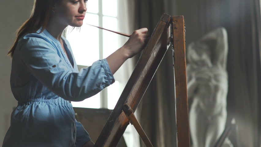 A young woman paints a painting on a canvas, standing behind an easel, in an atmospheric workshop with panoramic windows and an antique statue. Art academy or drawing school. Inspiration. Talent.