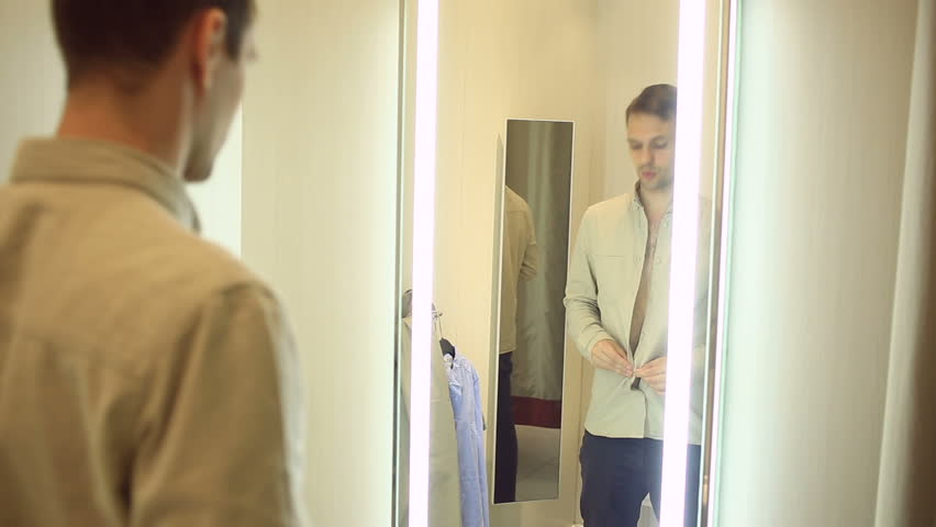 A man chooses clothes for himself in a clothing store. Trying on new clothes in the fitting room | Shutterstock HD Video #26322590