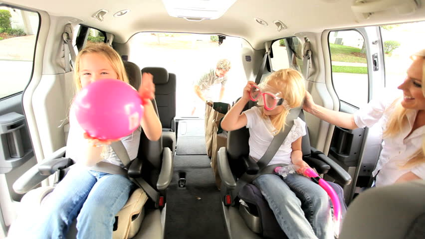 Young parents and children in family car preparing for beach vacation