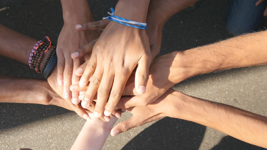 Arm of all races and colors stacked together one by one in unity and teamwork and then raised. Many multiracial hands getting together in the center of a circle and then cheer. Close up outdoor shot