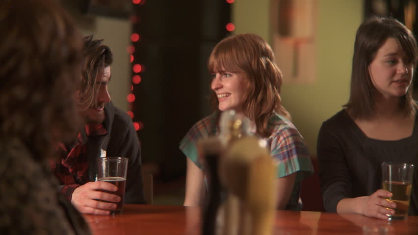 MS, PAN, Selective Focus, A woman ordering a beer at a bar and hanging out with her friends