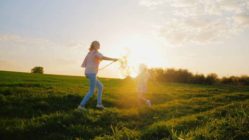 Activity at any age. A middle-aged woman is playing with her daughter, running around the field, having fun. Concept - a healthy lifestyle, a happy childhood