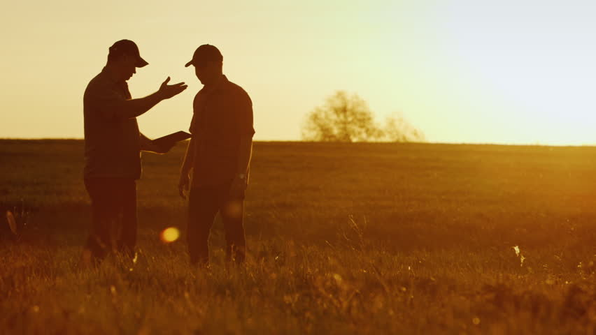 Two businessman farmers shake hands with each other firmly. They talk on the field against a beautiful sunset, they use a tablet. Deal   Shutterstock Video #26533409