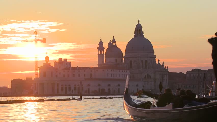 VENICE, ITALY-CIRCA 2011-A gondola is rowed by a gondolier in front of the setting sun in romantic Venice, Italy.