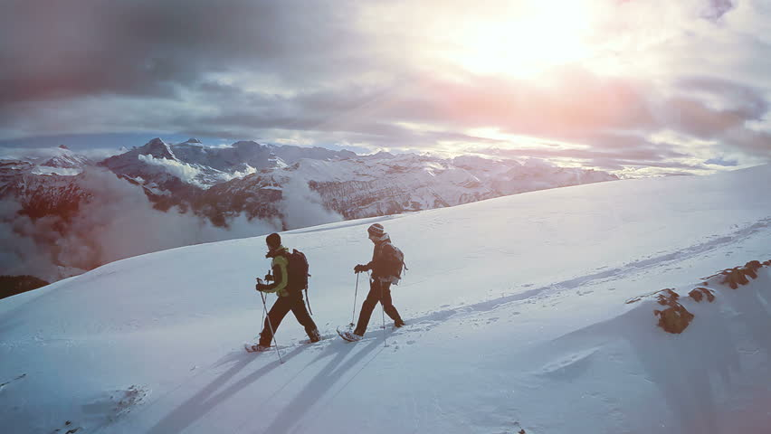 aerial view of two male hikers walking in untouched snow mountain landscape. aventures journey trip scenery of people climbing together on extreme winter expedition tour