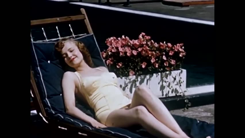 1950s: A 1950s woman relaxes in a reclining patio chair and is handed a bottle of Coke and a man playing horseshoes drinks as well.