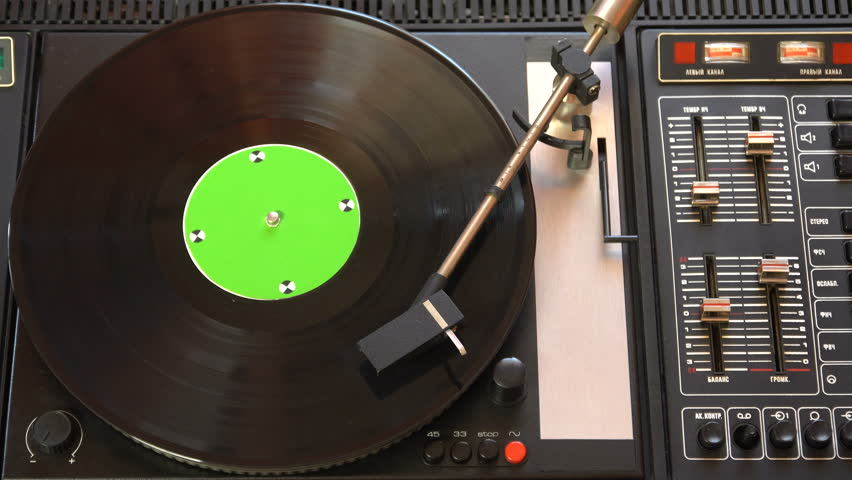Vinyl record pleer. Plays song from an old turntable 4k top view. Black background. Music round plate rotate. Music disc turn. Tracking shot rotating disk with chroma-key green screen. Tracking point.