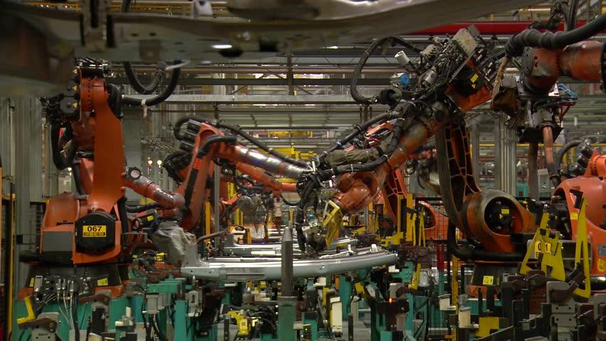 Robots are welding metal in car factory