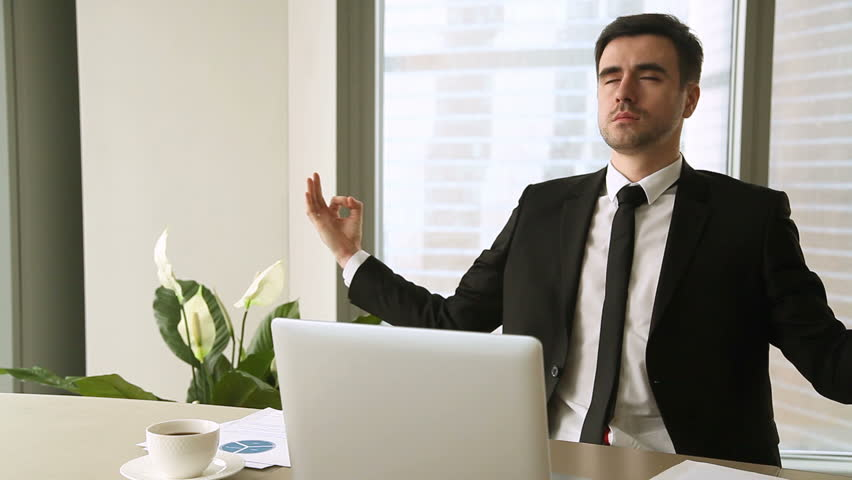 Young serious businessman working on laptop at office, meditating break at workplace with eyes closed, improving inner calm, implementing meditation to reduce stress at work, productivity hack concept