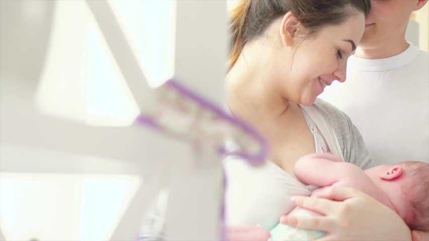 Happy young family with newborn baby. Mother, Father and New born Baby. Happy Mom and Dad kissing and hugging infant. Parenthood concept. Adoption. Slow motion 4K UHD video 3840X2160