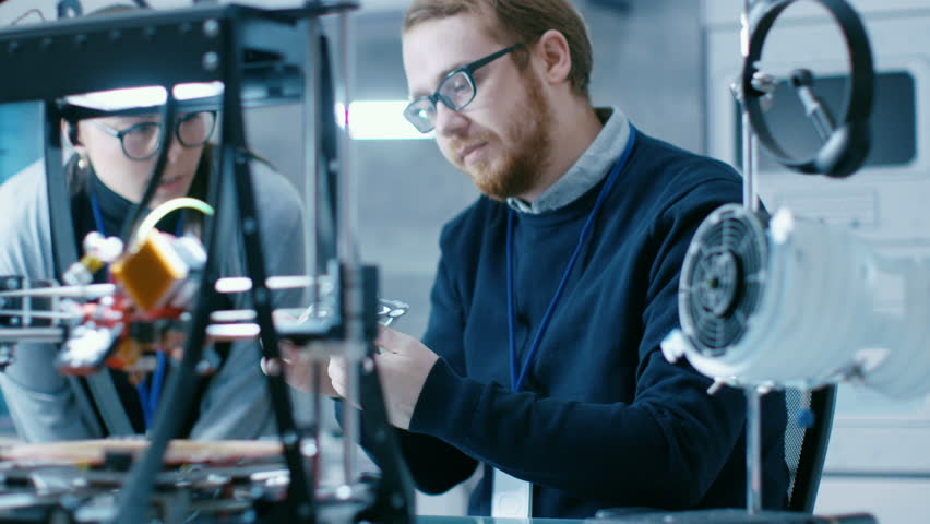 Young Talented Male and Female Engineers In a Modern Laboratory Construct Prototype with the Help of 3D Printer. Shot on RED EPIC-W 8K Helium Cinema Camera. Shot on RED EPIC-W 8K Helium Cinema Camera. | Shutterstock Video #27552184