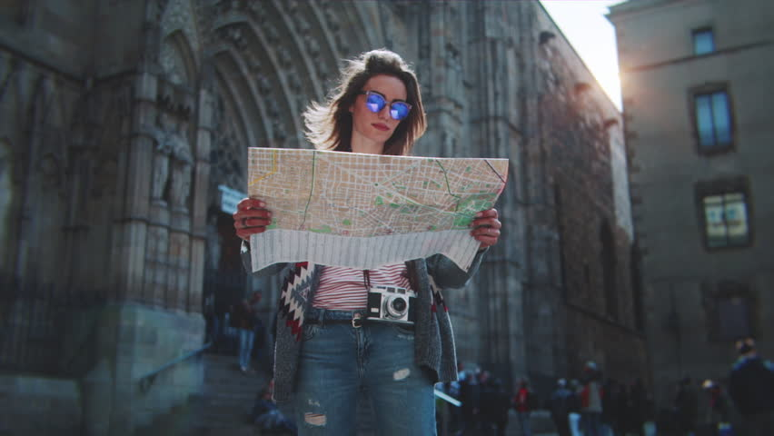 Attractive young woman traveling in Europe and exploring beautiful sightseeing in Barcelona, sunshine lens flare, slow motion, hipster girl wearing glasses and holding tourist map, enjoying holiday