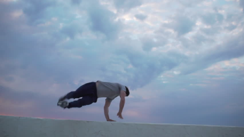 Young dexterous Caucasian male perfoming parkour exercises using parapet. Footage in slowmotion with cloudy sky