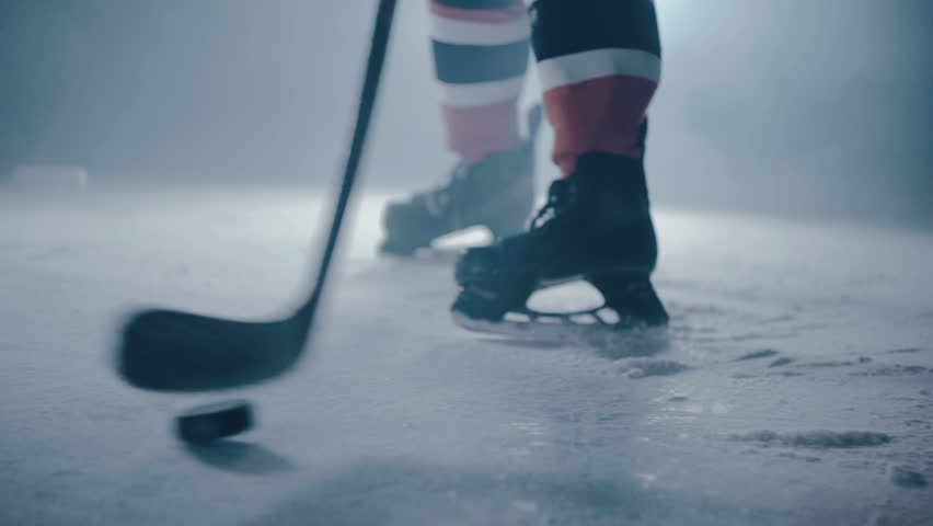 Hockey player hits the puck with a stick on ice close-up   Shutterstock Video #27736873