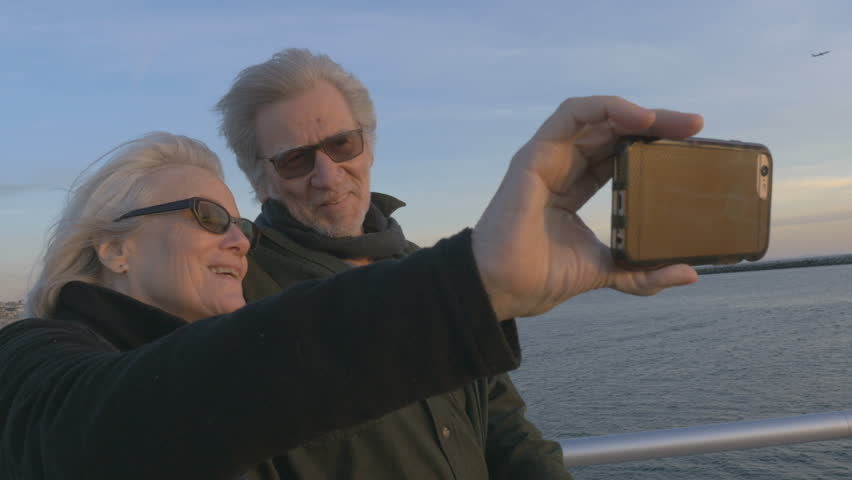 Attractive happy elderly couple in 60s take selfie with smartphone at sunset on ocean smiling and laughing together. Retired baby boomers using cell phone for photos and sharing on social media apps