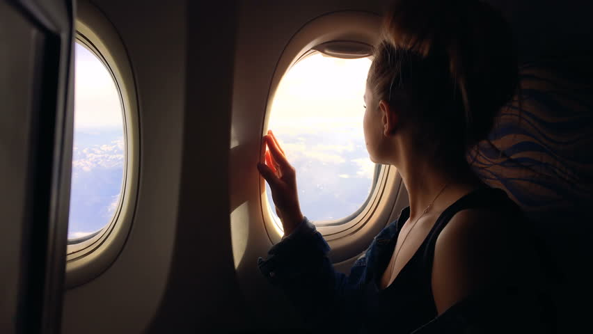 A young girl travels by plane and sits by the window and enjoys the view and then closes the porthole. 1080p | Shutterstock HD Video #27882865