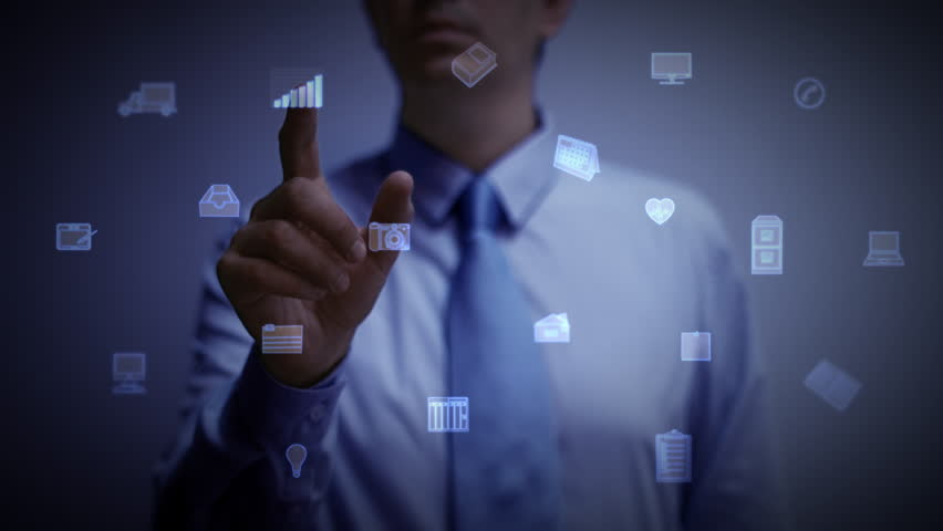 A businessman working on a blue holographic interface, touching a hologram showing a visual screen with computer and business icons. Financial charts and graphs appear. The touchscreen illuminates. 4K | Shutterstock HD Video #28036459