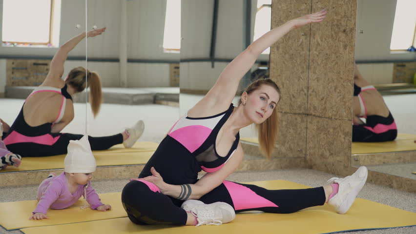 Young woman doing stretching exercise sitting near baby indoors. Brown haired lady dressed in black compression jumpsuit with bare back diligently and vigorously trains without parting with little