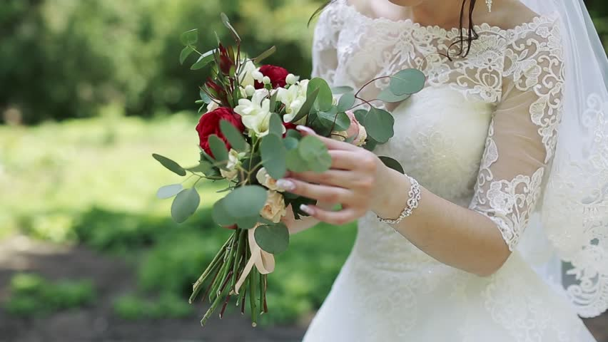 Beautiful bouquet of different colors in the hands of the bride in a white dress | Shutterstock HD Video #28103080
