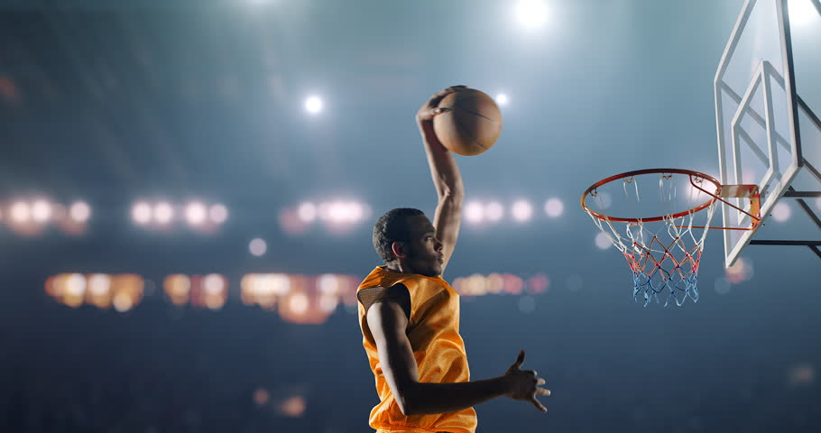 Close up image of professional basketball player making slam dunk during basketball game in floodlight basketball court. The player is wearing unbranded sport clothes. | Shutterstock Video #28198924