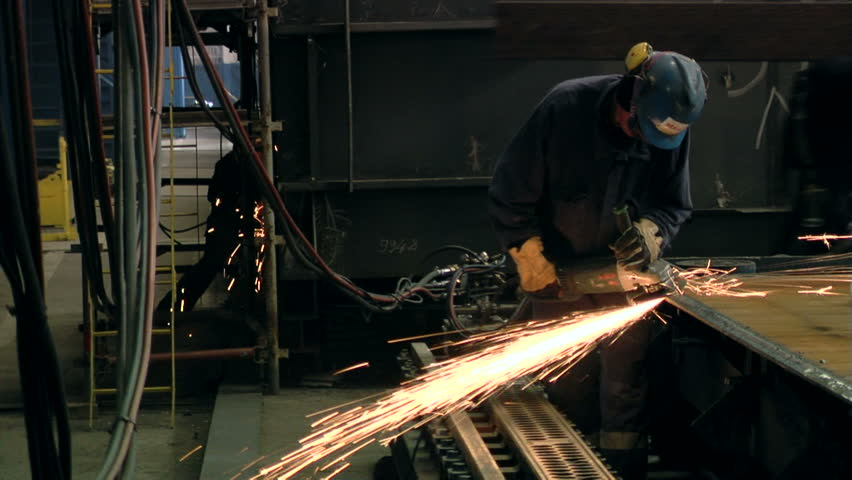 Man polishing in shipyard with protective equipment