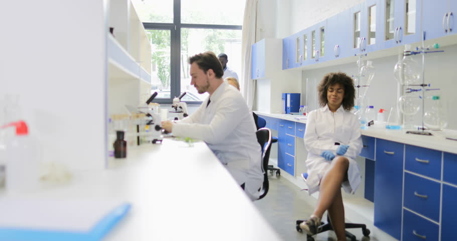 Group Of Scientists Working In Modern Laboratory, Two Colleagues Discuss Examples In Test Tubes Slow Motion 60 | Shutterstock HD Video #28396087