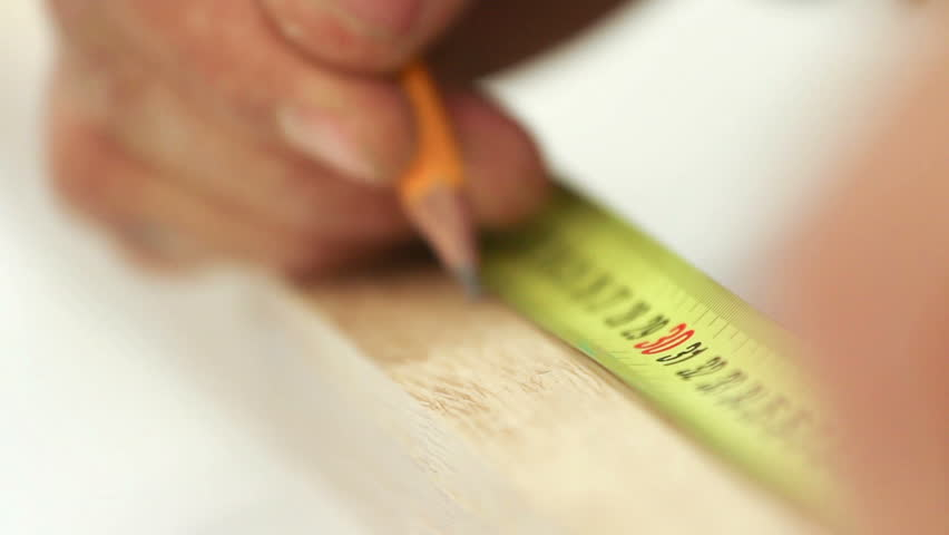 Carpenter working with tape measure,marking wooden desk (selective focus)