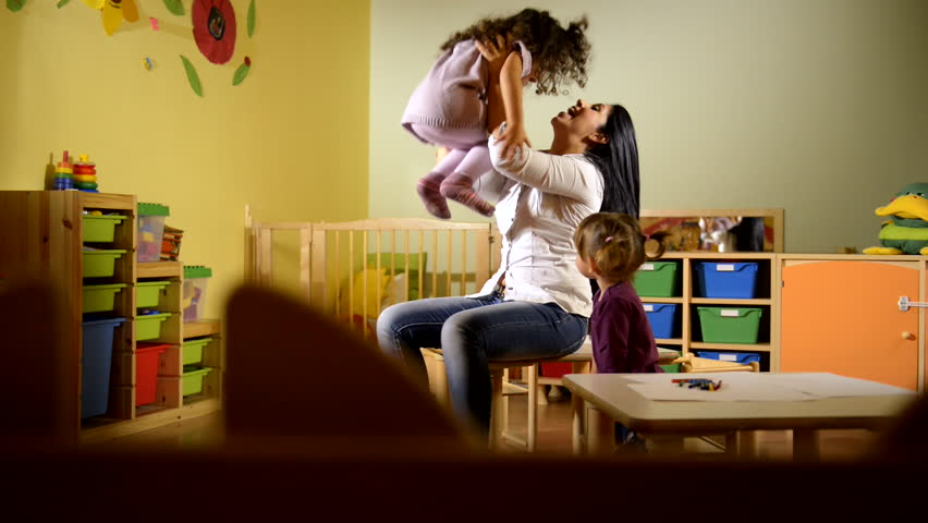People having fun at school, female teacher playing with child in kindergarten