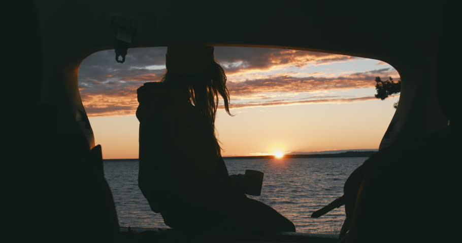 CINEMAGRAPH - seamless loop. CU Silhouette of young Caucasian female sits on a SUV trunk and enjoying hot drink on a lake during sunset. 4K UHD