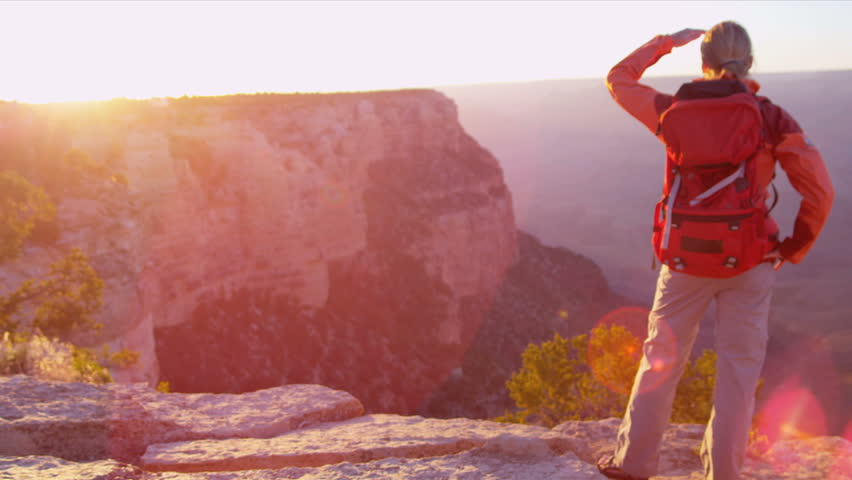 Lone female hiker watching the sun setting over the canyons, USA, Shot on Red Epic