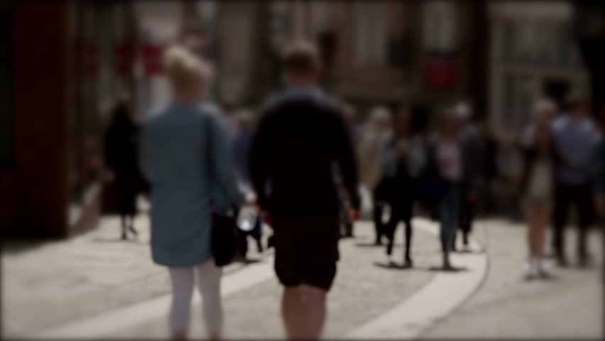 Blurred 4K video of crowds on busy high street. Summer shoppers etc. Cobbled street. Durham UK. Couple with shorts. Backlit.  #28931857