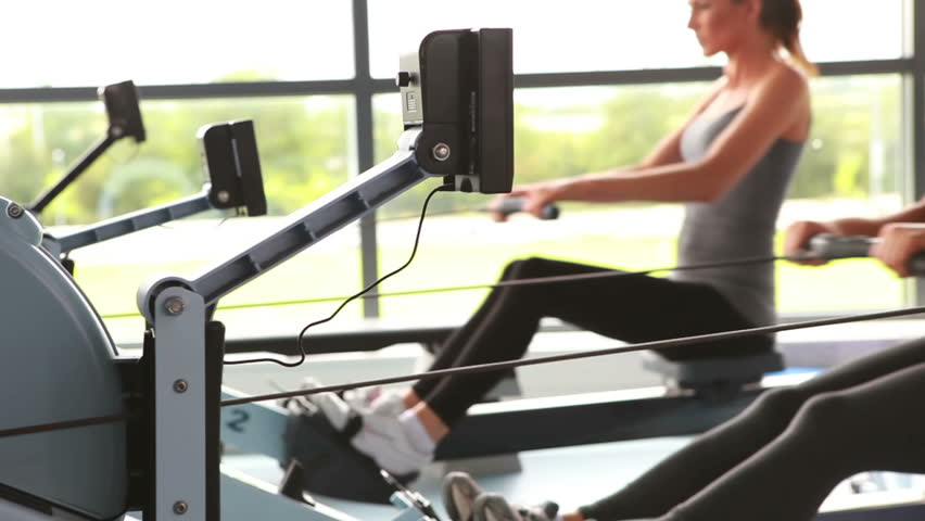 Women working out on rowing machine in gym