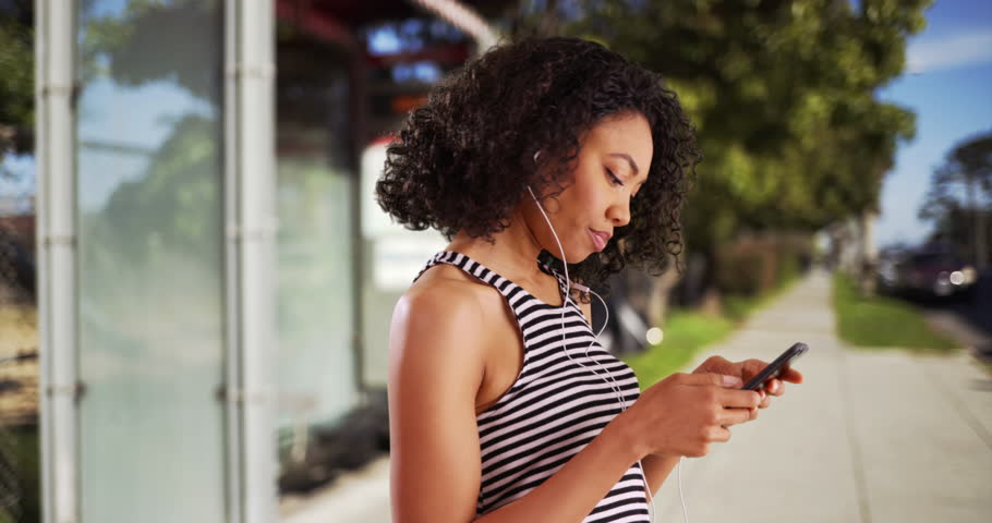 Profile of cute black female listening to cool song on cellphone, closing her eyes. Pretty African woman bobbing her head to music in outdoor setting on summer day. 4k | Shutterstock HD Video #29225212