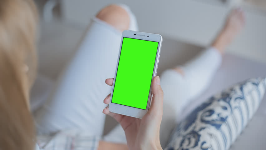 Young Woman in white jeans laying on couch holds SmartPhone with pre-keyed green screen. Perfect for screen compositing. Made from 14bit RAW. 10bit ProRes 444 | Shutterstock HD Video #29241532