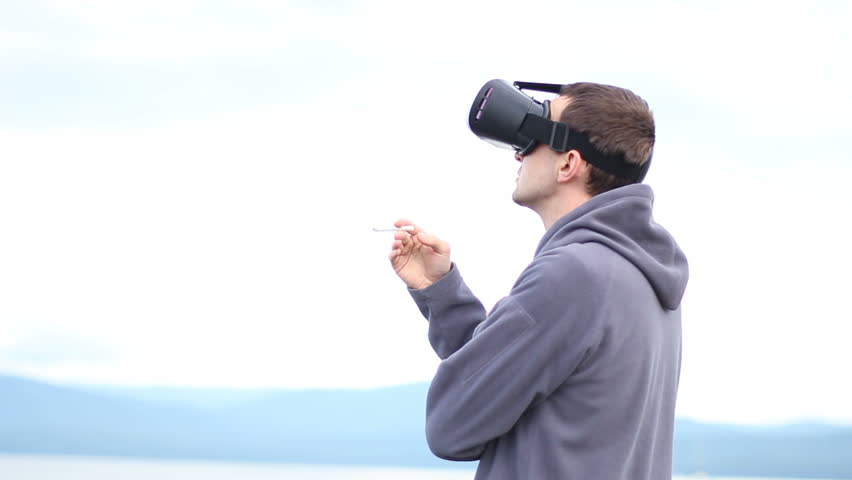 man uses a virtual reality glasses and smokes a cigarette against the sky and landscape.