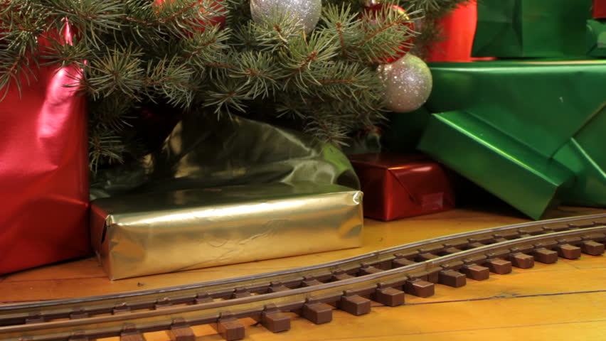 Toy electric train filled with decorations passes in front of christmas tree