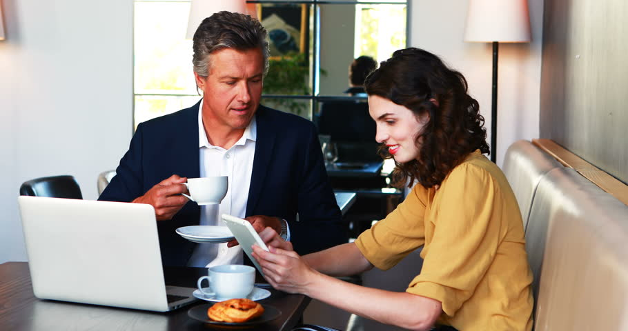Businessman and colleague discussing over digital tablet while having coffee in restaurant | Shutterstock HD Video #29391625