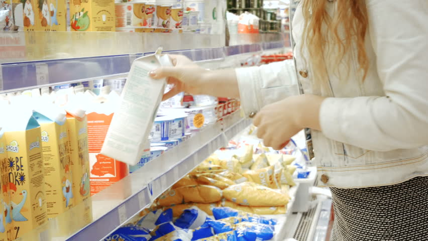 TERNOPIL, UKRAINE - JULY 15, 2017: Young woman in a dairy section of supermarket get a milk | Shutterstock HD Video #29430286