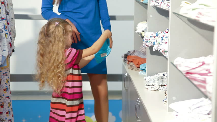 Mother With Two Daughters Shopping For Girls Clothes In A Clothing ...