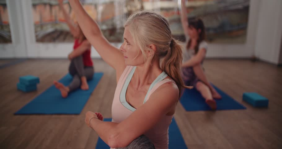 Active senior retired woman practising pilates and exercising in a yoga studio
