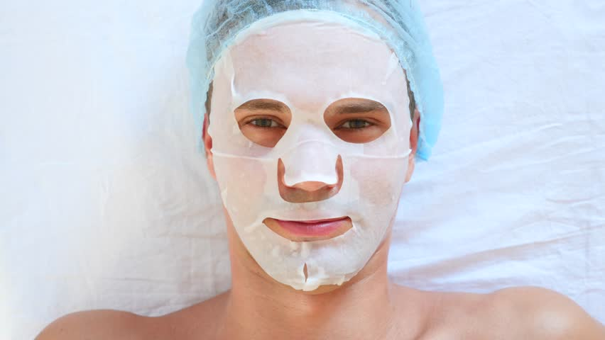 Spa therapy for handsome men receiving facial mask. 4k. Slow motion. Reception of a cosmetologist