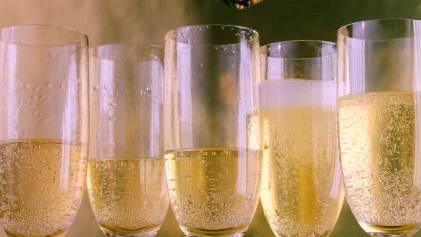Close up of bottle coming into frame to pour champagne into glasses
