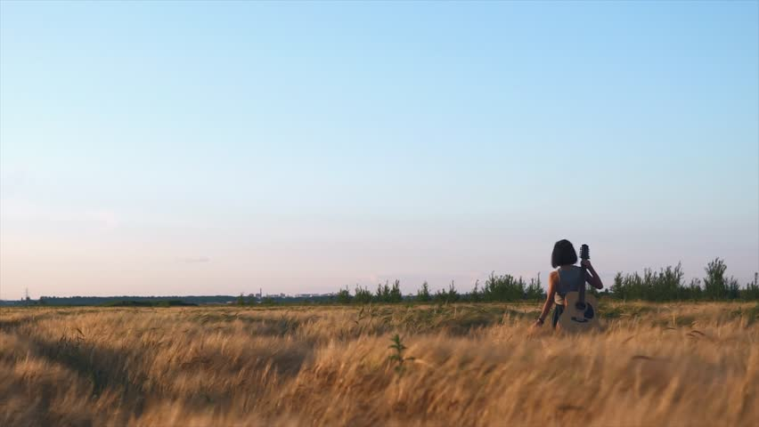 Lonely girl walking with a guitar at wheat field